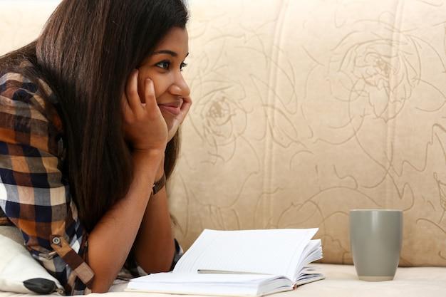 Sonriente mujer negra acostarse en el sofá con una taza de bebida caliente
