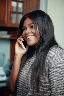 Sonriente mujer negra hablando por teléfono
