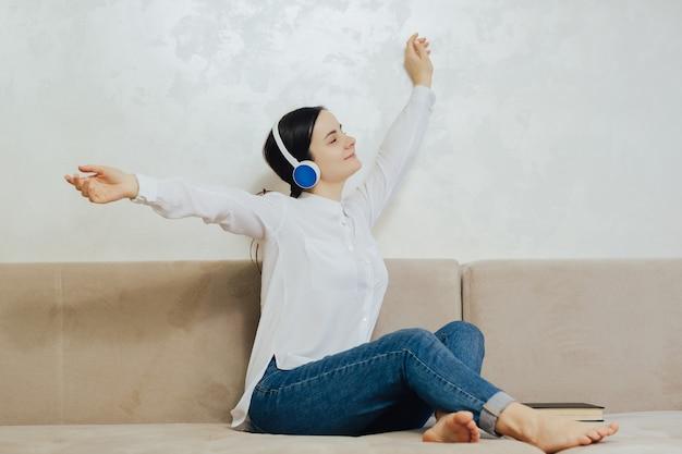 Sonriente mujer pacífica con las manos en alto relajándose y bailando en un cómodo sofá, escuchando su música favorita en modernos auriculares inalámbricos.