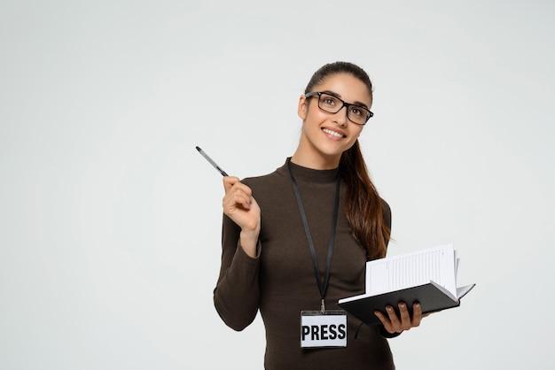 Sonriente mujer periodista escribiendo, entrevistando