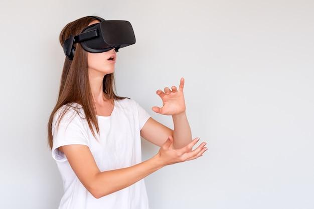 Sonriente mujer positiva con gafas de realidad virtual auriculares, caja vr. conexión, tecnología, nueva generación, concepto de progreso. chica tratando de tocar objetos en realidad virtual. foto de estudio en gris