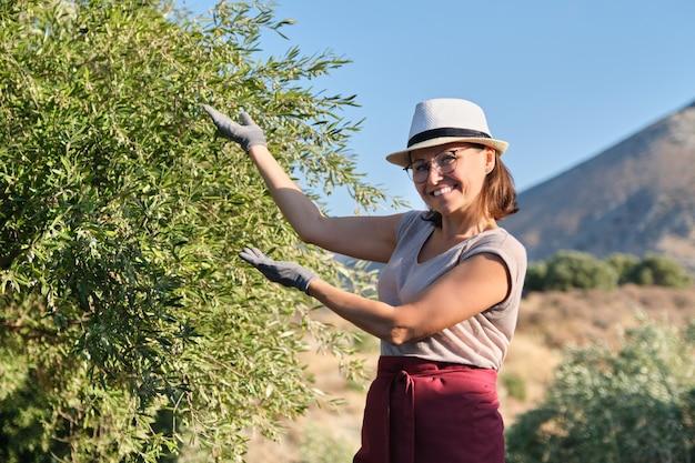 Sonriente mujer propietaria de un jardín de olivos apuntando a un árbol