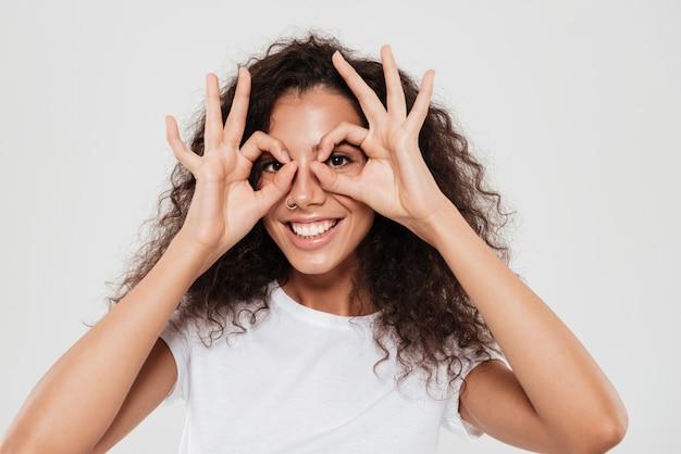 Sonriente mujer rizada cogidos de la mano en la cara y mostrando signos bien