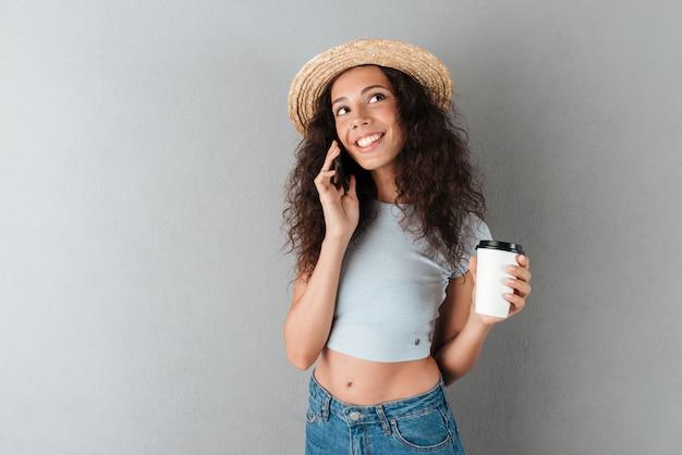 Sonriente mujer rizada con sombrero hablando por el teléfono inteligente con café en mano y mirando hacia arriba sobre fondo gris