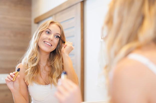 Sonriente mujer rubia aplicando rímel en el baño.