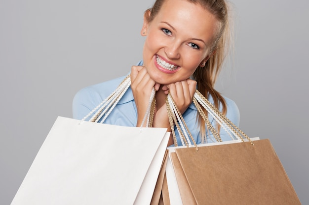 Sonriente mujer rubia con bolsas de compras ecológicas