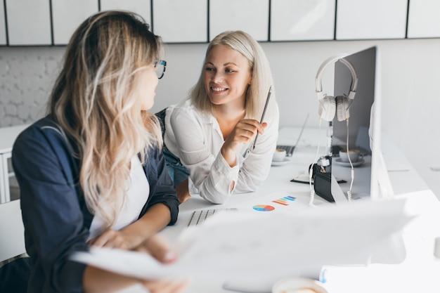 Sonriente mujer rubia de pelo corto hablando con su colega en la oficina mientras jugaba con lápiz. retrato de interior de mujer diseñadora web mirando a mujer alegre con camisa blanca.