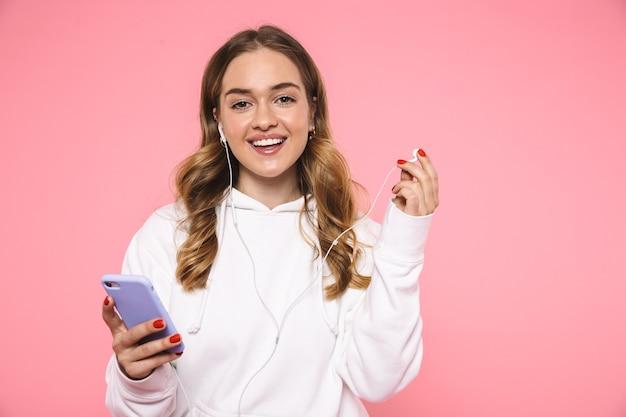 Sonriente mujer rubia vestida con ropa casual escuchando música y mirando al frente sobre la pared rosa