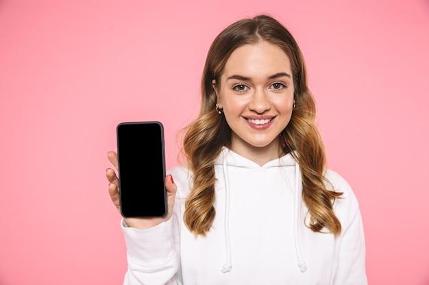 Sonriente mujer rubia vestida con ropa casual que muestra la pantalla del teléfono inteligente en blanco y mirando al frente sobre la pared rosa