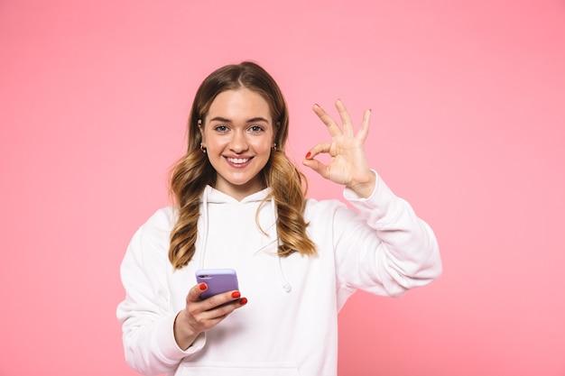 Sonriente mujer rubia vestida con ropa casual que muestra el signo de ok y mirando al frente mientras sostiene el teléfono inteligente sobre la pared rosa