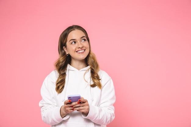 Sonriente mujer rubia vestida con ropa casual sosteniendo el teléfono inteligente y mirando hacia arriba sobre la pared rosa