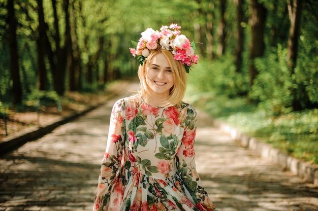 Sonriente mujer rubia vestida con vestido de flores y corona rosa en el parque