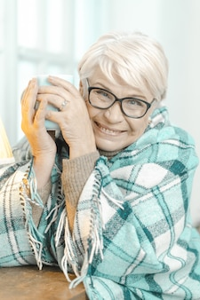 Sonriente mujer senior pensando en algo y sosteniendo una taza de té.