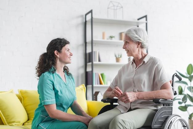 Sonriente mujer senior sentada en silla de ruedas mirando enfermera