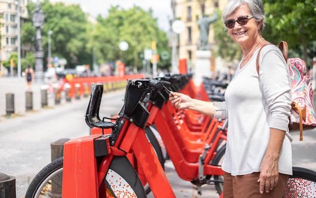 Sonriente mujer senior con tarjeta de crédito alquilando una bicicleta eléctrica en un parque público. jubilado casual feliz disfrutando de la libertad y el deporte