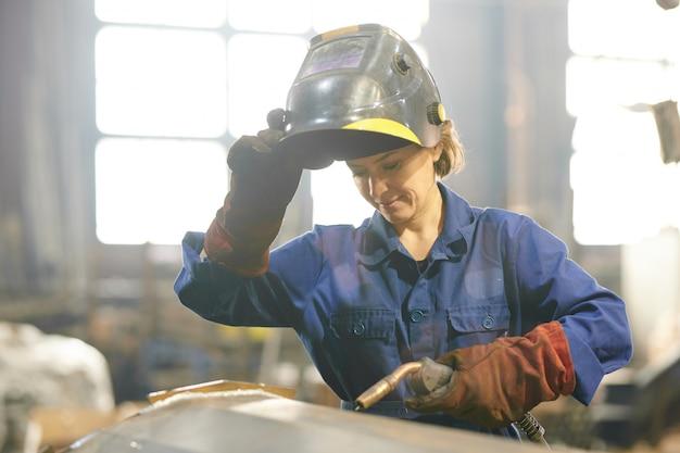Sonriente mujer soldador
