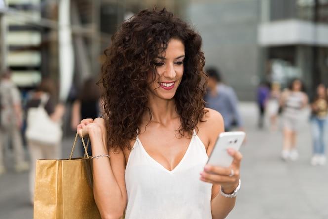Sonriente mujer sosteniendo bolsas de compras mientras usa su teléfono móvil