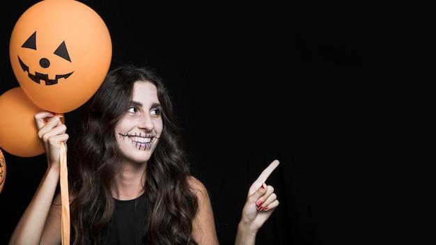 Sonriente mujer sosteniendo globos de halloween
