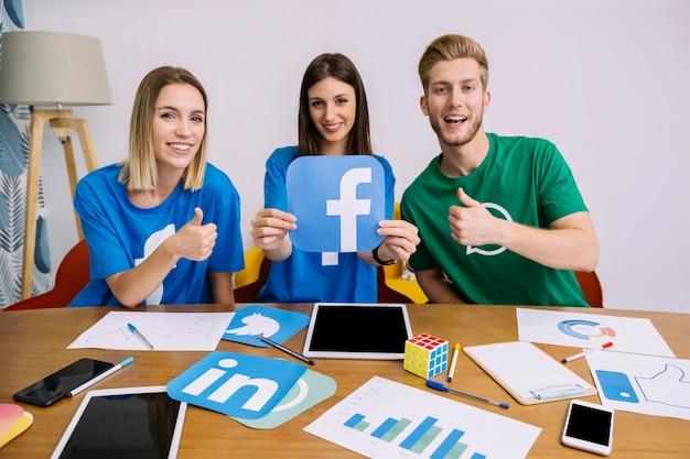 Sonriente mujer sosteniendo el logo de facebook con sus amigos mostrando signo thumbup