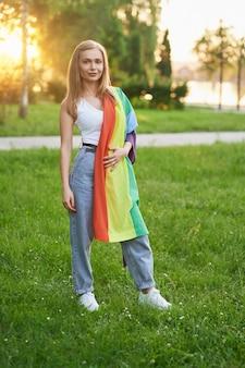 Sonriente mujer tolerante sosteniendo la bandera del arco iris lgbt