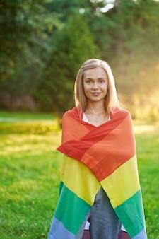 Sonriente mujer tolerante sosteniendo la bandera lgbt al aire libre