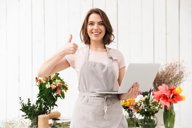 Sonriente mujer de ventas de pie cerca de ramos de flores en la tienda de flores y mostrando el pulgar hacia arriba con el portátil en la mano
