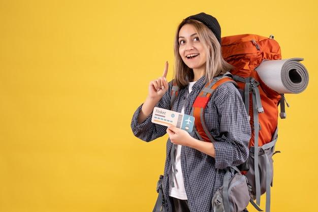 Sonriente mujer viajera con mochila sosteniendo el billete apuntando con el dedo hacia arriba