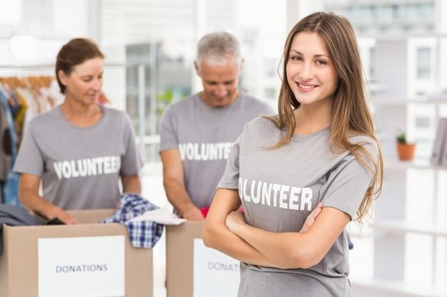 Sonriente mujer voluntaria con los brazos cruzados