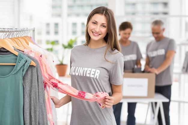 Sonriente mujer voluntaria eligiendo ropa