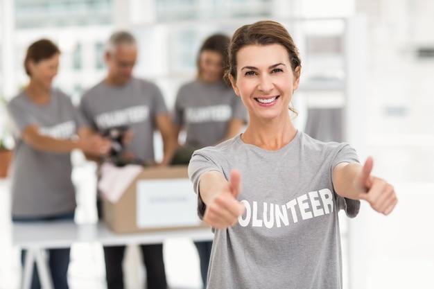 Sonriente mujer voluntaria haciendo pulgares arriba