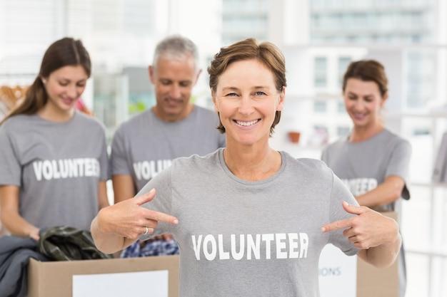 Sonriente mujer voluntaria señalando en la camisa