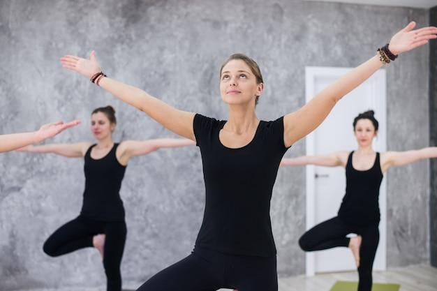 Sonriente mujer yogui en clase de asanas de yoga