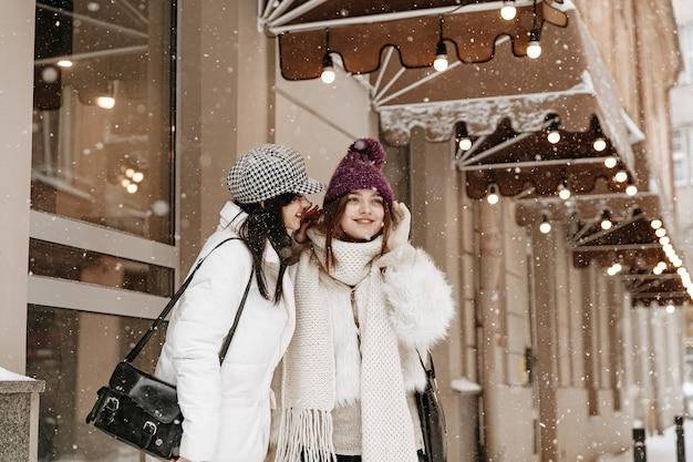 Sonriente a mujeres jóvenes vistiendo ropa de invierno abrigada charlando