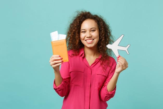 Sonriente niña africana en ropa casual con pasaporte, boleto de embarque, avión de papel aislado sobre fondo de pared azul turquesa. concepto de estilo de vida de emociones sinceras de personas. simulacros de espacio de copia.