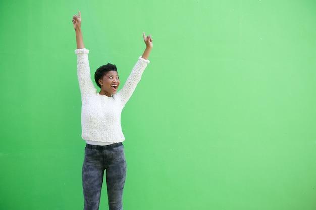 Sonriente niña afroamericana contra la pared verde