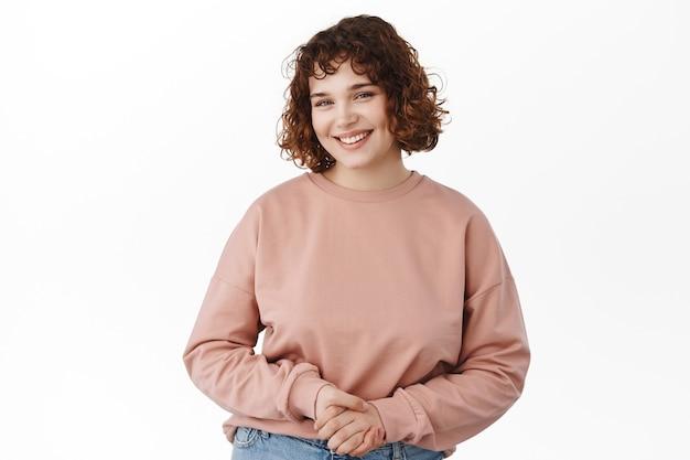 Sonriente niña amigable con el pelo corto, tomados de las manos juntas, luciendo optimista y sonriendo, ¿cómo puedo ayudarlo a posar, escuchando al cliente, de pie en blanco