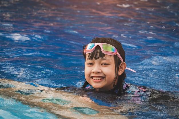 Sonriente niña asiática con gafas de sol en la piscina