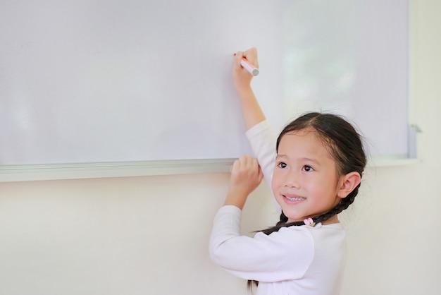Sonriente niña asiática niño escribiendo algo en la pizarra con un marcador