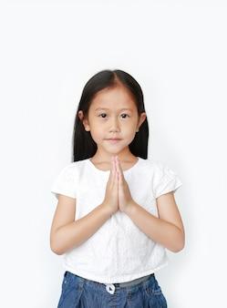 Sonriente niña asiática rezando
