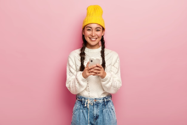 Sonriente niña bonita milenaria usa un teléfono móvil moderno, conectado a internet inalámbrico, descarga imágenes, verifica el buzón de correo electrónico, usa un sombrero amarillo