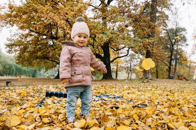 Sonriente niña de pie en el bosque de otoño