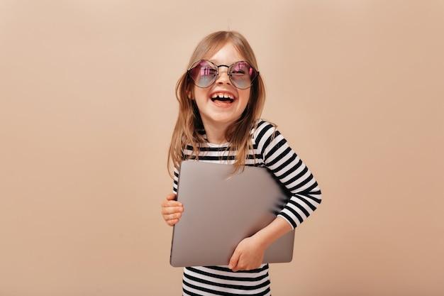 Sonriente niña emocionada con gafas y camisa despojada riendo y sosteniendo la computadora portátil