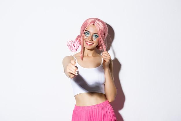 Sonriente niña encantadora con peluca rosa que le da dulces, celebrando halloween, truco o trato.