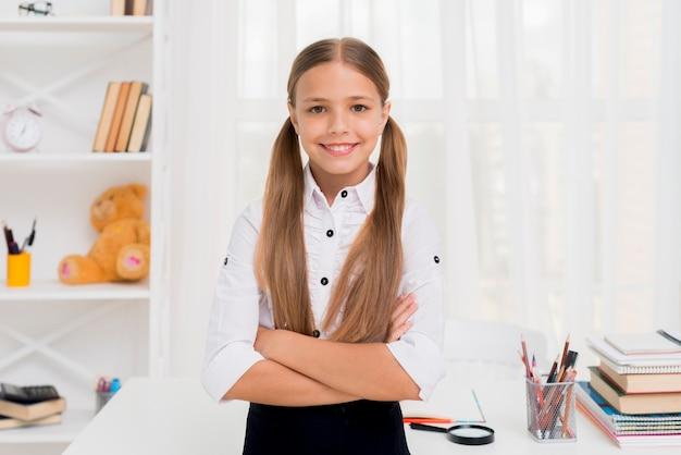 Sonriente niña de la escuela primaria de pie con los brazos cruzados