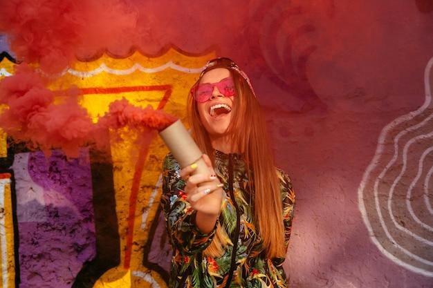 Sonriente niña feliz en gafas de sol con bomba de humo rojo, de pie cerca de la pared con graffiti.