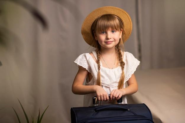 Sonriente niña feliz con un sombrero y una maleta con equipaje, una bolsa de viaje en sus manos se encuentra en una habitación de hotel, check in en el viaje del hotel y viaje al mar.