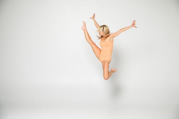 Sonriente niña gimnasta flexible en un traje haciendo ejercicios de estiramiento