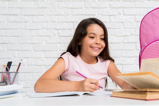 Sonriente niña hispana haciendo la tarea de casa