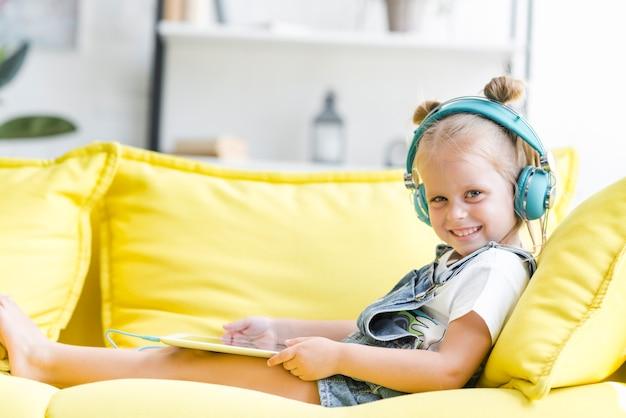 Sonriente niña linda en auriculares escuchando música con una tableta
