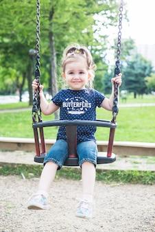 Sonriente niña linda sentada en columpio en el parque